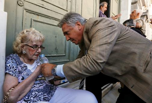 A pensioner is helped by a bank manager after collapsing while waiting along with dozens of other pensioners outside a National Bank in Athens, Greece, July 2, 2015. REUTERS/Yannis Behrakis