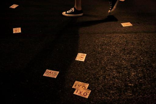 A demonstrator walks along a road with leaflets reading 'no' scattered on the ground, following a demonstration supporting the no vote on the upcoming referendum, outside of the European Union office in central Athens, on Thursday, July 2, 2015. (AP Photo/Petros Karadjias)
