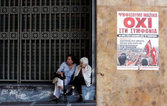 Women sit in front of the National Bank building next to a poster that shows the word 'No' in Greek in Athens, Greece, July 3, 2015. An opinion poll on Greece's bailout referendum published on Friday pointed to a slight lead for the Yes vote, on 44.8 percent, against 43.4 percent for the No vote that the leftwing government backs. REUTERS/Jean-Paul Pelissier