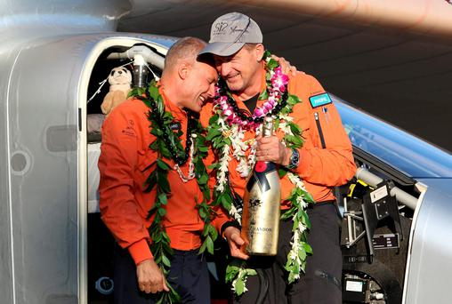 Bertrand Piccard (L) celebrates with Andre Borschberg after the Solar Impulse 2 airplane, piloted by Borschberg, landed at Kalaeloa airport after flying non-stop from Nagoya, Japan, in Kapolei, Hawaii