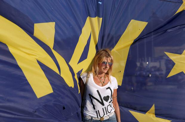 An activist is backed by a Yes flag as she campaigns in Athens