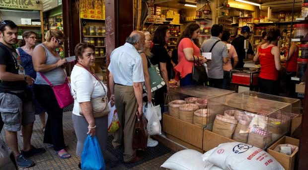 People queue to buy groceries in a shop in Athens