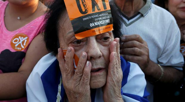 A woman wearing a No sticker on her face attends a rally in central Athens