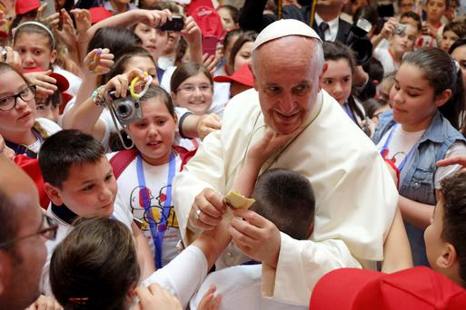 Children visiting from Naples swarm around the Pope to touch him and give him cards
