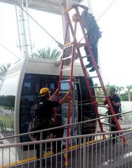 In this photo provided by Orange County Fire Rescue, a technical crew with The Orlando Eye Ferris wheel work to evacuated passengers after it stopped in Orlando, Fla., Friday, July 3, 2015. (Orange County Fire Rescue via AP)