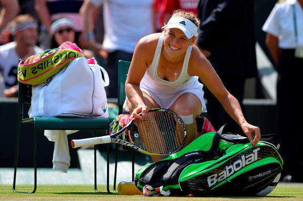 Denmark's Caroline Wozniacki smiles as she puts away her racquet after beating Italy's Camila Giorgi during their women's singles third round match on day six of the 2015 Wimbledon Championships