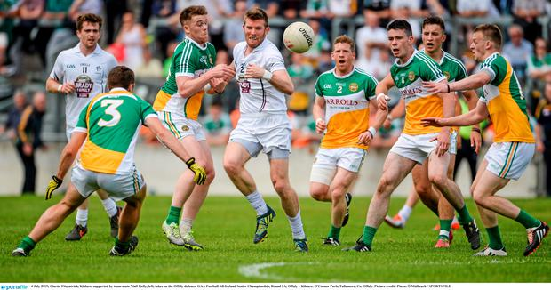 Ciaran Fitzpatrick, Kildare, supported by team-mate Niall Kelly, left, takes on the Offaly defence