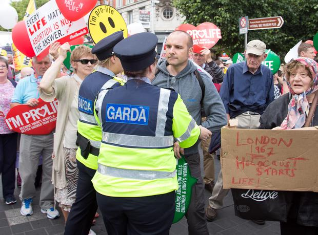 A Pro Life supporter is confronted by Gardai after he exchanged views with Pro Choice supporters during a march on O'Connell Street yesterday. Photo: Tony Gavin 4/7/2015
