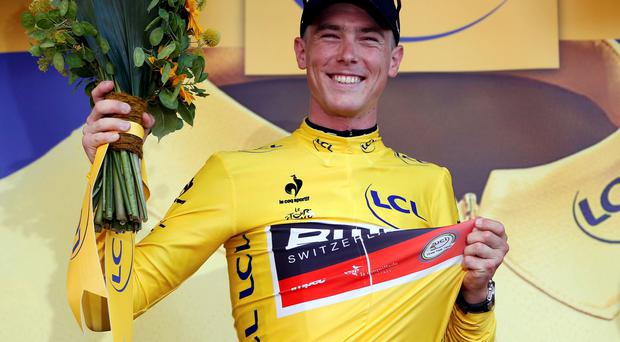 BMC Racing rider Rohan Dennis of Australia wears the race leader's yellow jersey on the podium after the 13.8 km (8.57 miles) individual time-trial first stage of the 102nd Tour de France cycling race in Utrecht, Netherlands, July 4, 2015. REUTERS/Eric Gaillard TPX IMAGES OF THE DAY