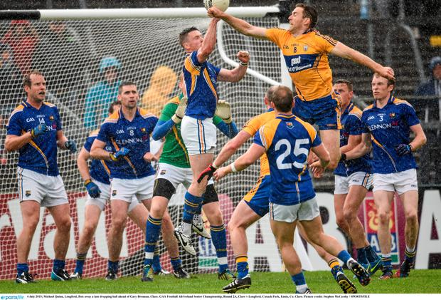Michael Quinn, Longford, fists away a late dropping ball ahead of Gary Brennan, Clare. GAA Football All-Ireland Senior Championship, Round 2A, Clare v Longford. Cusack Park, Ennis, Co. Clare. Picture credit: Stephen McCarthy / SPORTSFILE