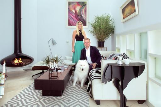 Suzie McAdam and Barry Byrne with their husky, Mischko, in their contemporary styled living room with its fire orb. Suzie has added vintage touches like the Eames rocker, and the cushions are made up in fabrics of her own design and are available from her website. Photo: Tony Gavin