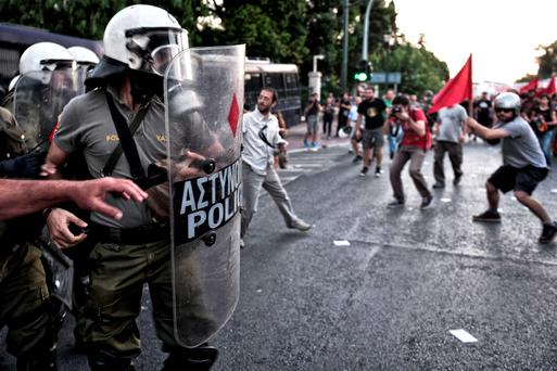 'Sneering at the Greeks seems to be the order of the day in certain circles right now' - Pictured police face anti-EU protesters in front of the European commision offices in Athens during a demonstration supporting the no vote for the upcoming referendum