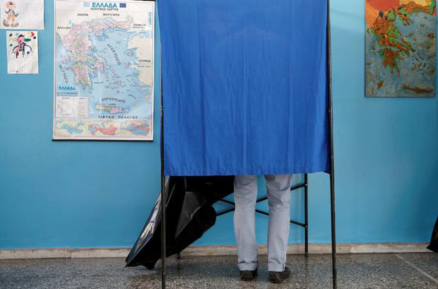 Maps of Greece hang on the wall next to a voting booth in a polling station at a school's classroom in Athens, Greece July 5, 2015. REUTERS/Yannis Behrakis