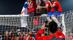 Chile celebrate with the trophy on the goal after defeating Argentina to win the Copa America 2015 final soccer match at the National Stadium in Santiago, Chile, July 4, 2015. REUTERS/Marcos Brindicci