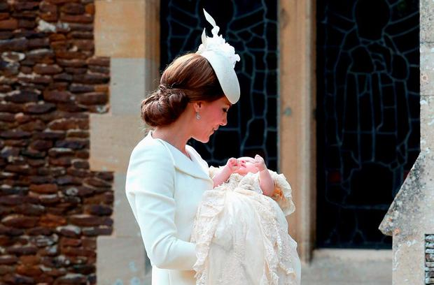 Britain's Catherine, Duchess of Cambridge, carries her daughter, Princess Charlotte of Cambridge after taking her out of a pram as they arrive for Charlotte's Christening at St. Mary Magdalene Church in Sandringham