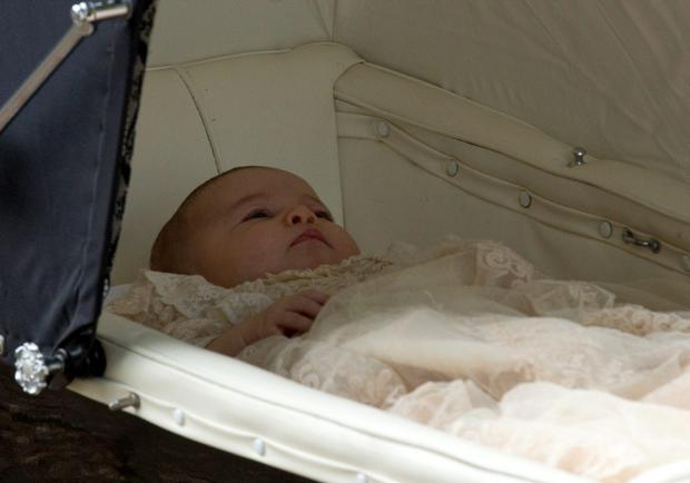 Princess Charlotte of Cambridge arrives in her pram, pushed by her mother Britain's Catherine, Duchess of Cambridge (not pictured), as they arrive for Charlotte's Christening at St. Mary Magdalene Church in Sandringham
