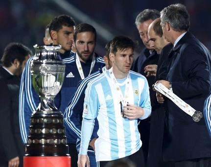 Argentina's Lionel Messi walks past the trophy after losing to Chile in the Copa America 2015 final soccer match at the National Stadium in Santiago