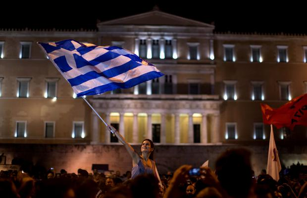 A supporter of the No vote waves a Greek flag in front of the parliament after the results of the referendum at Syntagma square in Athens, Sunday, July 5, 2015. (AP Photo/Emilio Morenatti)
