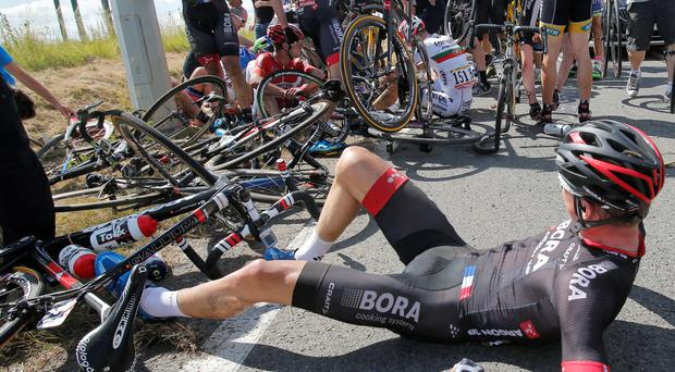 Riders get up after crashing during the third stage of the Tour de France Credit: Christophe Ena