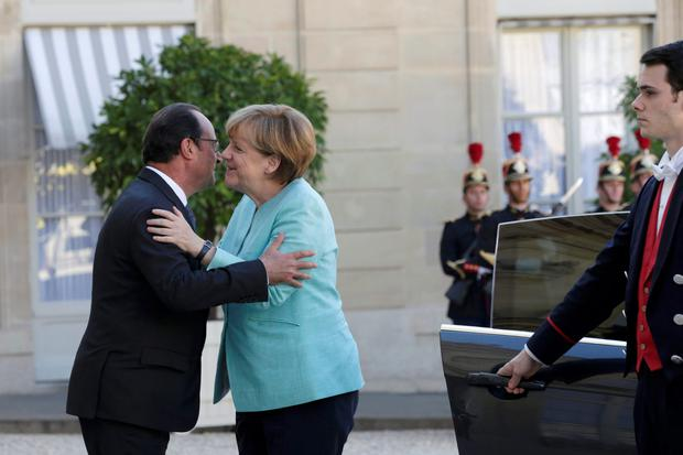 French President Francois Hollande (L) welcomes German Chancellor Angela Merkel before talks and a dinner at the Elysee Palace in Paris, France, July 6, 2015. Hollande and Merkel met in Paris on Monday evening following the Greek people's resounding 'No' to a European cash-for-reform deal in a referendum. REUTERS/Philippe Wojazer