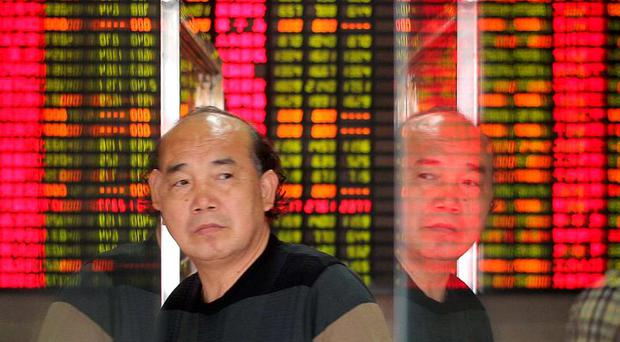 An investor is reflected on glass doors as he walks past in front of an electronic board showing stock information at a brokerage house in Shanghai, China. Photo: Reuters