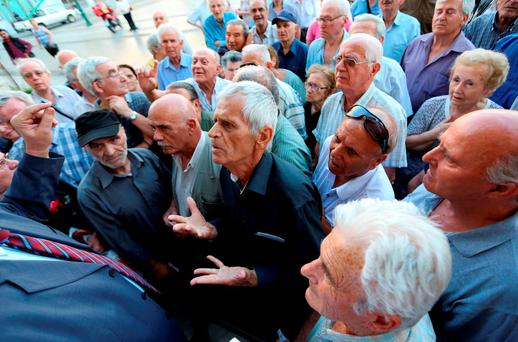 A pensioner argues with an official as he tries to enter a bank to receive part of his pension in Athens.