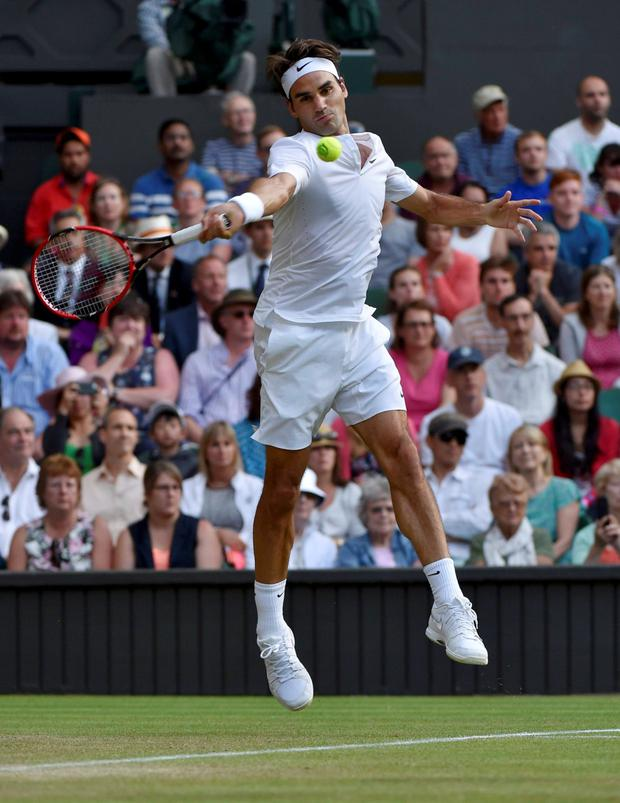 Roger Federer of Switzerland hits a shot during his match against Roberto Bautista Agut of Spain at the Wimbledon Tennis Championships in London, July 6, 2015. REUTERS/Toby Melville