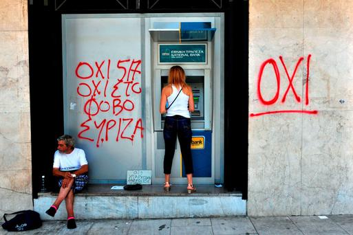 A woman withdraws money from an ATM machine next to a beggar and a graffiti reading