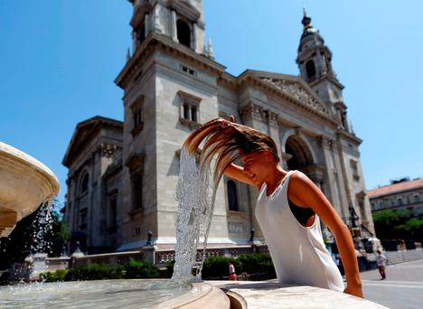 A woman dips her head into a fountain in Budapest, Hungary. Photo: Reuters
