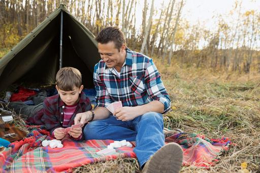 Father and son playing cards outside tent