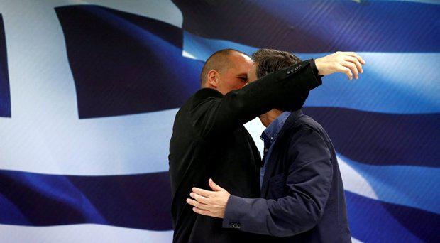 Newly-appointed Finance Minister Euclid Tsakalotos (R) and outgoing Yannis Varoufakis embrace at the Finance Ministry after a handover ceremony in Athens