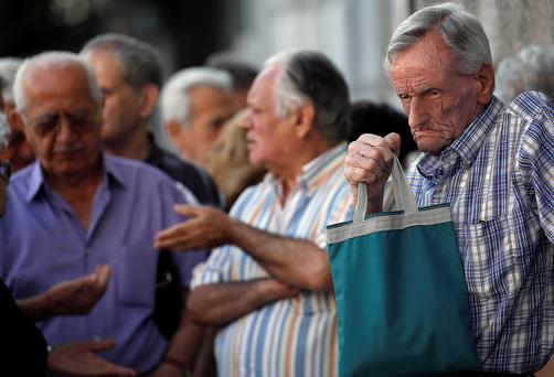 Pensioners wait outside a branch of the National Bank to receive part of their pension in Athens, Greece, July 7, 2015. Greece faces a last chance to stay in the euro zone on Tuesday when Prime Minister Alexis Tsipras puts proposals to an emergency euro zone summit after Greek voters resoundingly rejected the austerity terms of a defunct bailout. REUTERS/Yannis Behrakis
