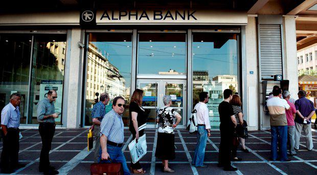 People queue at an ATM to withdraw cash in Athens on July 7, 2015. European Commission head Jean-Claude Juncker said that he was against an exit by Greece from the euro, even though Greeks massively rejected bailout terms in a referendum this weekend
