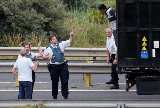 French policemen ask a migrant to get out of the trailer of a truck he climbed in, during an attempt to make a clandestine crossing to England through the Channel tunnel as lorries wait on a road which leads to the Channel Tunnel terminal in Coquelles near Calais Credit: REUTERS/Vincent Kessler