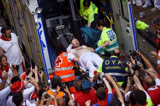 An injured runner gives a thumbs up as he is attended by medical personnel after being gored by a ''Jandilla'' fighting bull at the San Fermin Festival in Pamplona, Spain (AP Photo/Alvaro Barrientos)