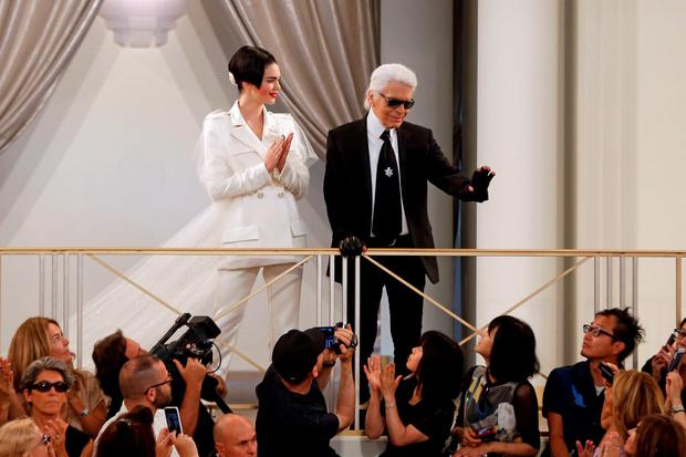 German fashion designer Karl Lagerfeld acknowledges the public with US model Kendall Jenner during the Chanel 2015-2016 fall/winter Haute Couture collection fashion show