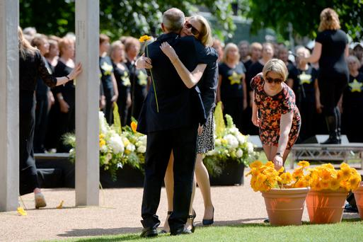 People hug each other as they collect a flower to leave at the July 7 memorial in Hyde Park, London, during a service in memory of those who died in the 7/7 bombings, as Britain remembers the July 7 attacks amid a welter of warnings about the enduring and changing threat from terrorism a decade on (Anthony Devlin/PA Wire)