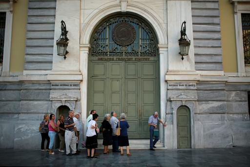 Senior citizens queue up to collect their pensions outside a National Bank of Greece branch in Kotzia Square