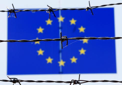 An EU flag behind barbed wire at an immigration centre in Hungary