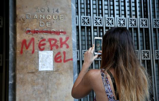 A tourist takes a picture outside the Greek Central Bank