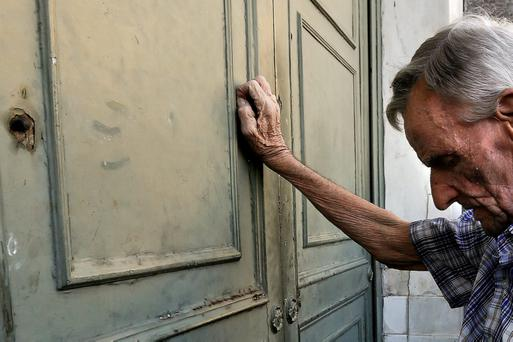 A pensioner waits outside a branch of the National Bank to receive part of his pension in Athens yesterday