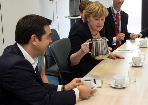 German Chancellor Angela Merkel pours a cup of coffee as Greek Prime Minister Alexis Tsipras looks on at a meeting with European Commission President Jean-Claude Juncker and French President Francois Hollande prior to an emergency summit in Brussels yesterday. Photo: Reuters