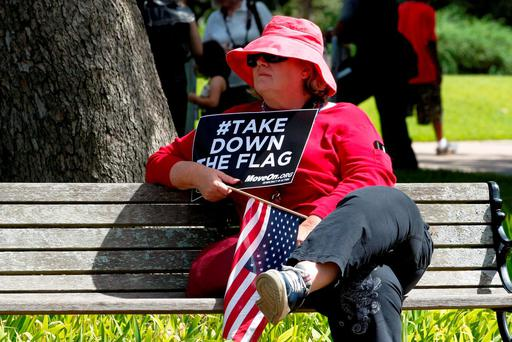 Barbara Beeler sits on a bench as she protests against the Confederate flag at the South Carolina State House in Columbia, South Carolina. Photo: Reuters