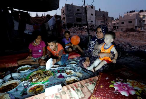 A Palestinian family gathers for a meal amid the rubble of buildings a year after the 50-day war between Israel and Hamas militants in the summer of 2014. Photo: Getty Images