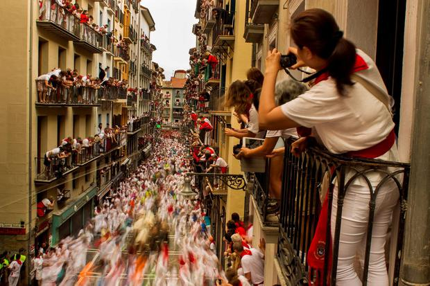 People watch as El Tajo y La Reina fighting bulls and revelers run during the running of the bulls, at the San Fermin festival, in Pamplona, Spain, Wednesday, July 8, 2015. Revelers from around the world arrive to Pamplona every year to take part in some of the eight days of the running of the bulls. (AP Photo/Andres Kudacki)