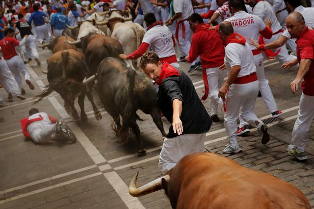 A reveler calls the attention of an 'El Tajo y La Reina' ranch fighting bull as others keep running during the San Fermin festival in Pamplona, Spain, Wednesday, July 8, 2015. Revelers from around the world arrive in Pamplona every year to take part in the event. (AP Photo/Daniel Ochoa de Olza)