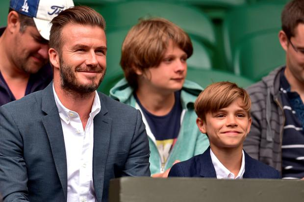 Former England footballer David Beckham (L) and his son Romeo (R) take their seats on centre court to watch the men's singles quarter-final match between Britain's Andy Murray and Canada's Vasek Pospisil on day nine of the 2015 Wimbledon Championships at The All England Tennis Club in Wimbledon, southwest London, on July 8, 2015. RESTRICTED TO EDITORIAL USE -- AFP PHOTO / LEON NEALLEON NEAL/AFP/Getty Images