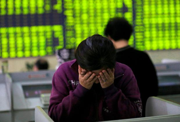 A woman rubs her face as she stands at a computer terminal in a stock brokerage house in Nantong in eastern China's Jiangsu province. Photo: AP