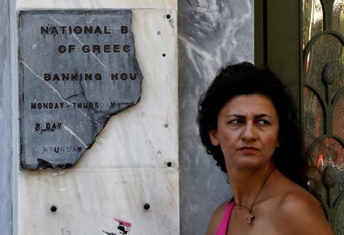 A Greek woman pauses by a broken marble National Bank sign outside a branch in Athens yesterday