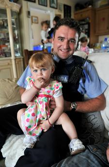 Analise McDonagh, 19 months old, gets a cuddle from Garda Joe Quinn three months after she was seriously injured in a car accident at her grandfather's home in Kilbannon, Tuam County Galway. Photo: Ray Ryan.